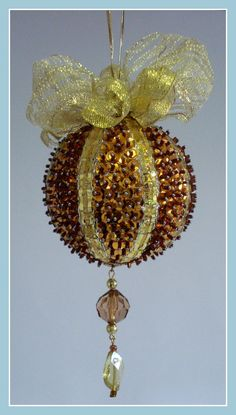 Pingente natalino confeccionado com bola de isopor, lantejoulas, pedrarias, miçangas, laços e fitas.