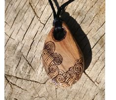 I carved this pendant from a piece of driftwood I found on Findhorn Beach (North-East Scotland). After carving I burned swirly sea designs into it using a technique called pyrography. Then I applied a lacquer finish.  It is about 55mm (just over 2in) long and on a silk cord tied with adjustable knots - the cord extends from 80cm (32in) circumference to 40cm (16inch) circumference. Please specify the length of cord you would like when you order, if not I will make it about 18 inches (450mm)…