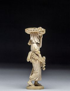 JAPANESE CARVED IVORY FLOWER LADY, MEIJI PERIOD (1868-1912) With a basket of flowers and fungi on her head and a bouquet of flowers under right arm; signed.  Dimensions: Height 9 1/8 in. (23.2 cm.)