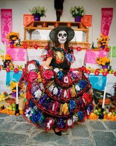 Lady dressed for Dia de los Muertos standing in front of altar (ofrenda).