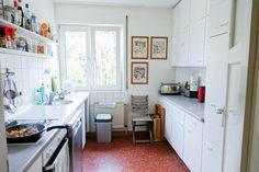 Helle Stuttgarter Küche mit weißen Möbeln, rotem Bodenbelag und großem Fenster.  Gemütlich kochen in Stuttgart.  #Stuttgart #Küche #kitchen #Wohnen