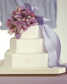 Use a pretty monogrammed cake as the pedestal for a cluster of anemones, tulips, lilacs, sweet peas, stephanotis, and allium tied with luxurious taffeta ribbon. Before the first slice is cut, the bride can retrieve the bouquet for the ceremonial toss. By Wendy Kromer.