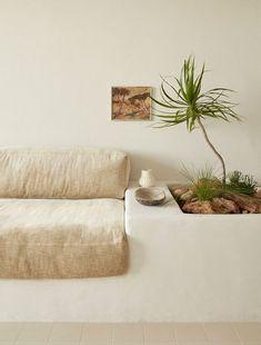 Esprit maison de plage pour ce coin salon simplement meublé avec un canapé intégré
