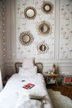 Gorgeous toddler girl room in a Parisian apartment. White walls, mouldings, flamingo wallpaper and vintage round gold mirrors on the wall