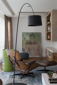 Confira o cantinho da leitura nesse apartamento cheio vida, com poltrona Eames e luminária Lumini.