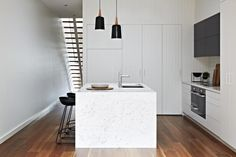 White modern kitchen with beadboard wall of cabinets and refrigerator, marble-like waterfall island, sleek induction cooktop with under oven / micro. | desire to inspire - desiretoinspire.net
