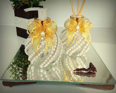 Kit para decoração e perfume para banheiro ou lavabo, contem 2 vidros de 110 ml cada, sendo:  Aromatizador de ambiente aroma suave, acompanha 4 varetas.  Sabonete líquido neutro,  ambos os vidros com tampas douradas, decorados co strass, pérolas e laços de fita dourado.  A BANDEJA NÃO ACOMPANHA O...