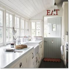 Galley kitchen with wall of windows and adorable dutch door