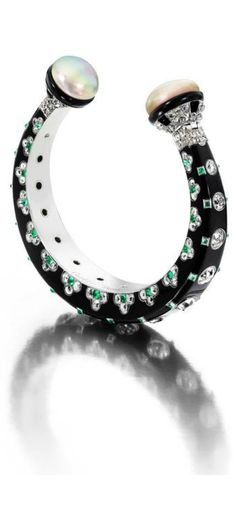 This magnificent Cartier bracelet, exhibited at Masterpiece London by Siegelson, boasts the symmetry and bold colour that defined the Art Deco period. The bracelet, in tapered black lacquer, is set with diamonds and emeralds and has natural pearls at either end of the open closure.