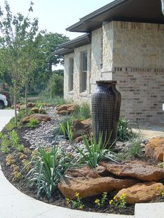 Small boulders, cobblestone drainage dry creek bed, decorative pots, and strategically placed native plant material give a modern feel to this xeriscape landscape design in Flower Mound, Texas. By One Speciality.