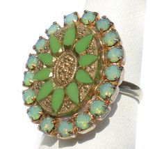 This beautiful ring features a very detailed center of green glass with gold accent, all surrounded by an oval of stunning rhinestones. It really is