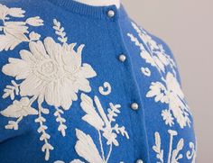 A rare, gorgeous sweater via Helen Bond Carruthers, the ultimate name in decorated cardigans. Carruthers cut her embroidery pieces from 1920s piano shawls and antique linens and then expertly attached them to cashmere cardigans. Each design is unique, intensively decorated, and simply stunning. She also usually tailored the sleeve cuffs and waistband by tacking them in, and attached a lovely silk chiffon lining. This particular sweater is reminiscent of Wedgewood porcelain with its beautiful…