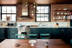 The kitchen - AD España, © blocksy.com Encimera de mármol y mobiliario de madera en la cocina, que ha sido completada con accesorios de Wolf and Sub-Zero.
