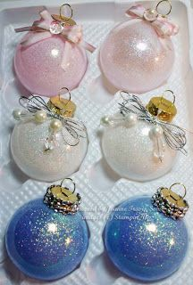 Clear glass balls (available at most craft stores), coated inside with thin glue called Glitter It, then added glitter with a small funnel and embellished.  Can also use a floor wax to get the glue to stick. Any thin, pourable glue will do as long as it is fairly clear.