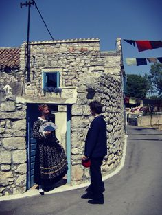 Still of young couple dressed in traditional clothes in front of an old stone house in Jezera, island Murter.