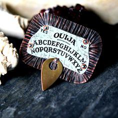 Part of my new Halloween Collection, The Spirit Board Line, this is a brooch made from 19 gauge copper sheet and a tin image of a ouija board. The copper back has been textured and measures 1 3/4 x 2