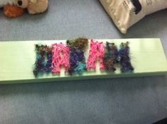"""I made this to hang next to my bed. You can't tell in the picture but the board is painted green. First I painted the board then I hammered the nails to say """"dream"""", then I took some yarn (purchased at the local flea market) and ran it in a random pattern between the nails. I hope you enjoy this fun project!"""