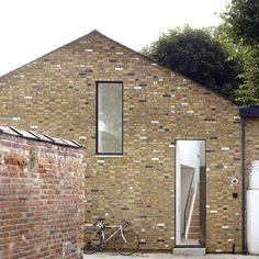A gabled brick facade with a three-metre-high door fronts this former mews house in east London, renovated by architect Cassion Castle as a private studio for a photographer.
