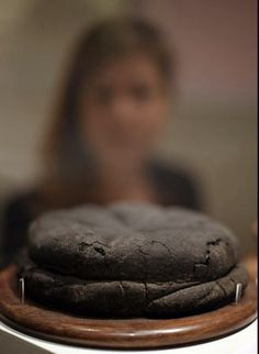 A load of Roman bread, carbonized at Pompeii. Based on the person looking at it, how big was it?