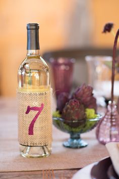 Bottles of ONEHOPE Wine double as table numbers and self-serve beverages. An aborigine number is stenciled on a burlap bottle sleeve to mimic the colorway and rusticity of the tablescape. Photo Courtesy of Allyson Magda Photography.