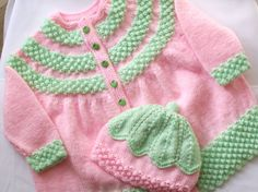 hand knitted baby cardigan / jacket with matching hat has five tiny green strawberry buttons size chest 22 inches length 14 inches circumference of hat 15 inches for baby or reborn knitted with new yarn I have several different designs of booties and hats for sale and can also custom make to the colours of your choice  ..    Thankyou for visiting