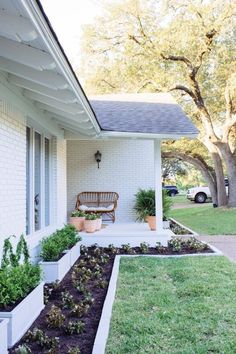Tidy flower beds coupled with planter boxes bring this classic exterior to life. For a clean look, Claire Brody painted the brick liner around the fresh beds in the same color as the exterior trim. Click to see the rest of this striking curb appeal makeover.