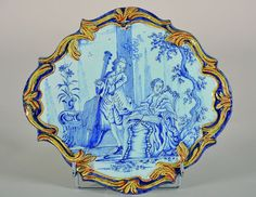 DELFT  Plaque en faïence de forme contournée, décor camaïeu bleu de deux personnages jouant de la musique  XVIIIe siècle  Haut. 27 cm - Larg. 30 cm.
