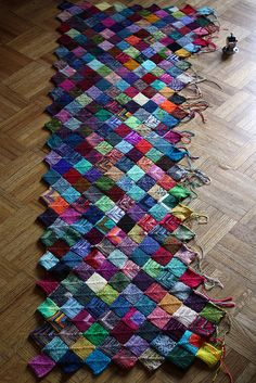 "Kiirsi Hellewell says:  The knitter making this blanket calls it an ""Insanity Blanket"" because it's tons of tiny squares made from sock yarn (very thin yarn). Looks like each square is knitted from donated yarn. See her link here: http://www.flickr.com/photo..."