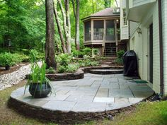 In an effort to maintain the intimacy of this wooded backyard, a space with two levels of entertaining was created. The upper screened-in porch is connected to the lower flagstone patio with large fieldstone steppers. These two tiers seem to be woven into the mature landscape. A dry creek was also installed to provide better drainage.