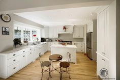 A Great Transitional Kitchen With Crisp White Cabinets, Stunning Natural Marble Countertops And Touches of Embellishment