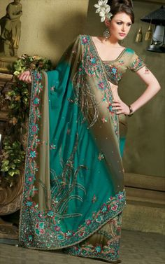 Indian saree' designs are spectacular, and individual. This one has a lot of embellishment  and character. The color is an amazing teal green, with gold. The outfit is chastised to every detail, and are hand made. Majestic and Sensitive !!!