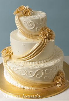 Golden Rose Drapes #18Drapery  This ivory buttercream three tier cake is decorated with swirls and swiss dots that are made from buttercream. Each layer is accented with a gold lustered fondant drape and golden gum paste roses.