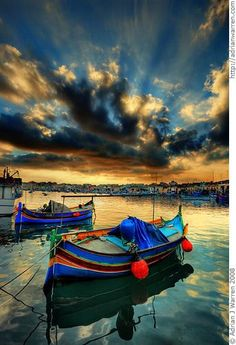Brightly coloured fishing boats, known as Luzzus, at Marsaxlokk, Malta.