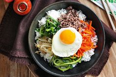 Bibimbap - 1 Lebanese cucumber, 3 t sea salt, 1 1/2 cups spinach, 1 T sesame oil, 1 1/4 t sesame seeds, 1 cup bean sprouts, 2 cups Sun Rice Sushi Rice, 1 1/2 T vegetable oil, 2 carrots, 300g lean beef mince, 4 eggs, Chilli sauce, Miso soup