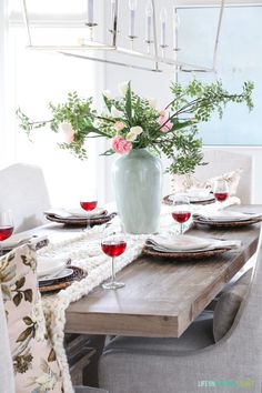 Valentine's Day table setting on a reclaimed wood dining table, with ivory chunky knit table runner, pink floral pillows, and heart shaped plates. Love the peony, tulip and greenery floral centerpiece.  #valentinesday #tablescape
