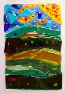 Great layering and inlay, this landscape has a variety of hues and surfaces created by adding confetti and frit.  Caitlin F was open to the magic of fusing with embellishing and experimenting! Very nice work by one of our youngest students.