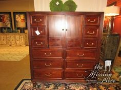 """Traditional style tall chest in a medium finish. This chest has twelve drawers! Excellent amount of storage space. There is a shelf behind the doors in the center as well as TV cutout. 56""""L x 20""""D x 64""""H."""