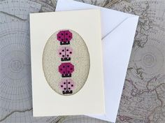 A small handmade card: 3 1/2 by 5 1/2 inches (just under 9 cm x 14 cm)   Happy pink ladybugs indark and light pink, in a cream coloured card with an oval shaped window.