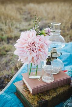 A single pink dahlia and old hurricane lamps atop a stack of vintage books | Photo by Amy Lynn Photography