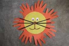 León con papel de colores y moldes con las manos de nuestros niños.