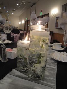 Wedding centerpiece with cylinder vases, orchids and floating candles