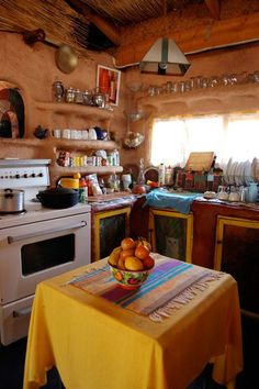 """ Marcella's Miracle Cob House. This South African home was built by hand for less than $5000, and the inside is so warm and beautiful. The kitchen makes us want to just sit down, have a cup of tea, and start planning dinner."""