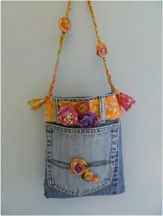 Upcycled blue jean handbag - made out of salvaged pieces of old jeans, leftover fabric, and embellished with handmade fabric rosettes.  Small size makes it fun for any age.
