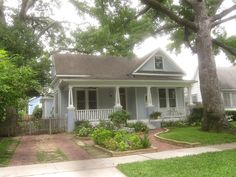 This front yard includes a cottage garden. Cottage gardens come in all styles. This cottage garden shares the yard with a nice lawn and tree. The inviting brickwork and walkway draws the eye to the beautiful front porch.
