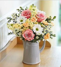 Charming Wishes Bouquet Send someone special a charming surprise for any reason… or no reason at all! This simple yet stylish arrangement of pink roses, white daisy poms, orange mini carnations and mo                                                                                                                                                      More