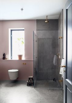 Delicate and raw shower cabin with pink tones and gray stones.