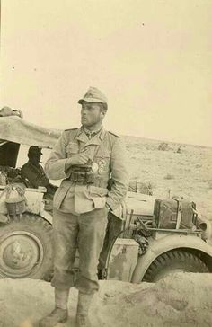 A soldier standing next to his staff car while serving with the Afrika Korps German Soldiers Ww2, German Army, Afrika Corps, North African Campaign, Erwin Rommel, Ww2 Uniforms, Italian Army, Panzer, Luftwaffe