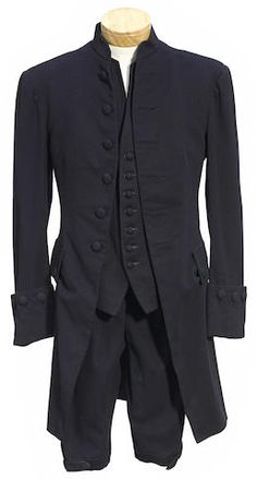 A Henry Fonda suit from Drums Along the Mohawk 20th Century Fox, 1939. Comprising a navy blue wool collarless overcoat with self-covered buttons; a navy blue wool vest; a pair of navy blue wool breeches with gilt metal buttons.