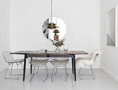 Dining table with mixed chairs. White floorboards and walls.