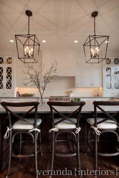 Love the pendant lighting.... White shaker style kitchen, with cross mullions on glass doors, dark floors and pendant lighting